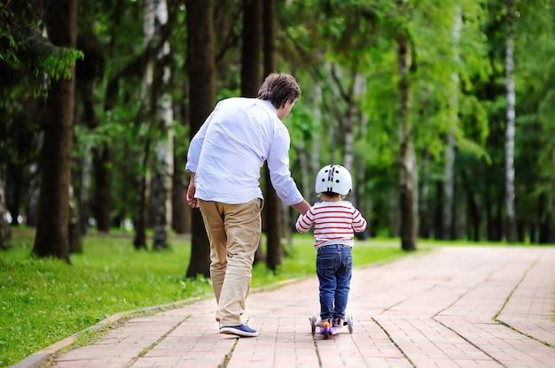 夏の公園でスクーターに乗る方法を彼の幼児の息子を示す中年父