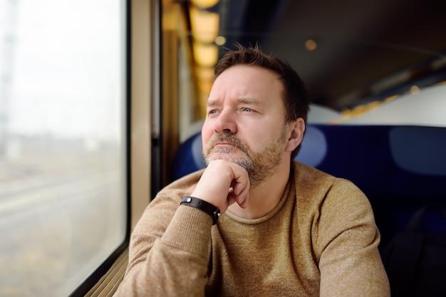 電車の窓から外を見て中年男