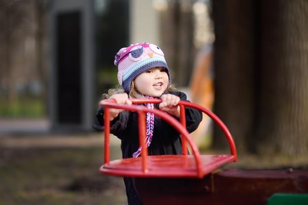 屋外の遊び場でカルーセルを楽しんでいる女の子