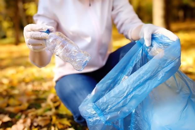 Волонтер собирает мусор и кладет его в биоразлагаемый мусорный мешок на улице.