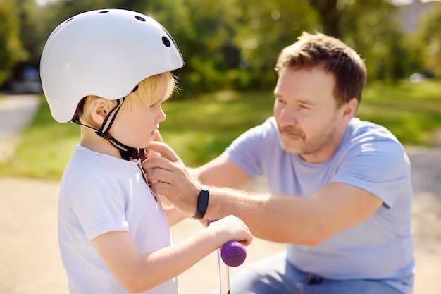 彼の幼い息子が彼のヘルメットをかぶるのを助ける中年父親。スクーターに乗るアクティブな男の子