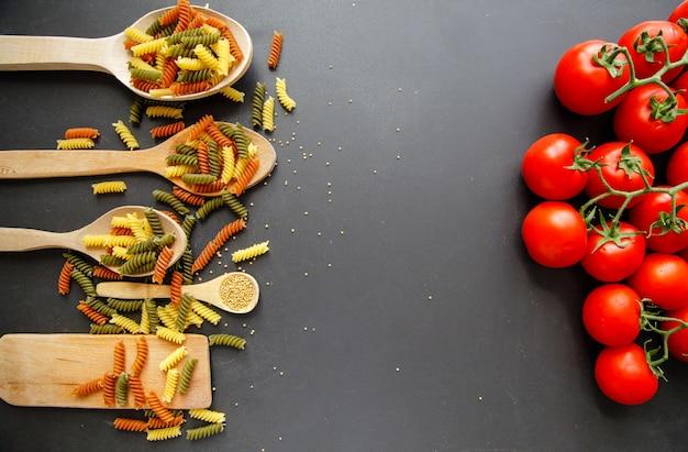 マカロニは黒の背景に分離しました。イタリア料理のコンセプトです。
