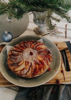 松の木の枝の花瓶とテーブルの上のクリスマスフルーツのパイ