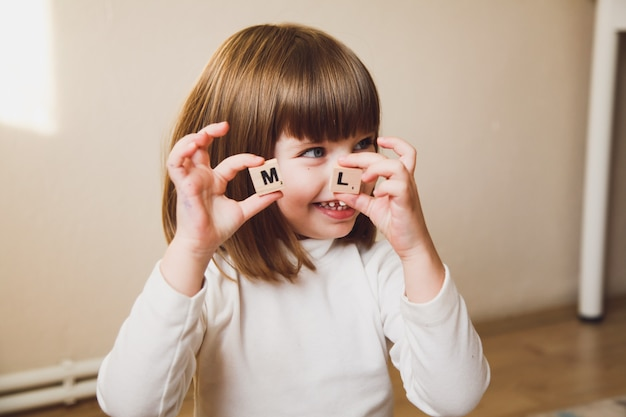 Маленькая кавказская девушка держа деревянные письма перед ее лицом. раннее развитие концепции ребенка.