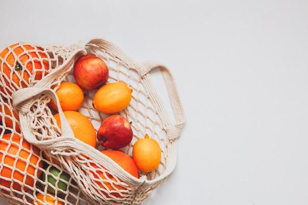 Спелые плоды в сеточку крючком на белом пространстве. концепция здорового образа жизни. концепция доставки.