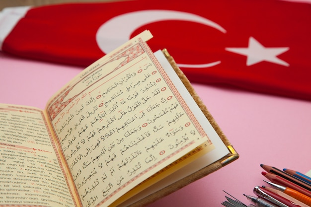 ピンクのテーブルにコーランとトルコのフラグ。アラビア語の概念。