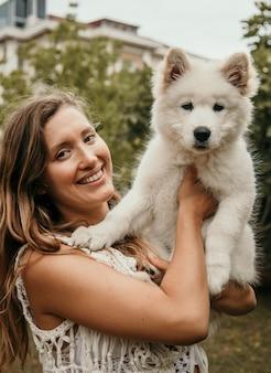 サモエドの子犬を彼女の腕で保持している白人の女性の笑みを浮かべてください。