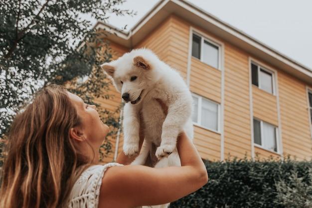 サモエド犬の子犬を手に持って外に立っている若い女の子。ペットのコンセプトを持っています。かわいい動物のコンセプトです。