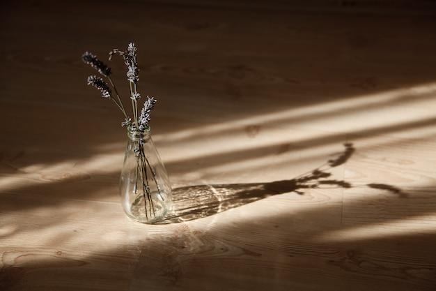 日光の下でガラス瓶の中のラベンダーの茎