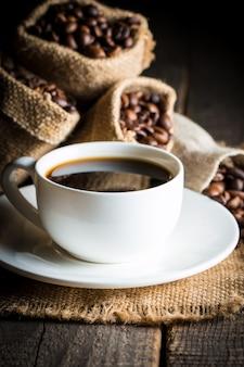 コーヒーカップと素朴な背景の上の豆。