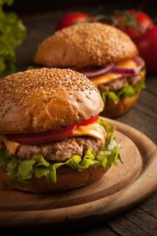 Гамбургер с говядиной, луком, помидорами, листьями салата и сыром.