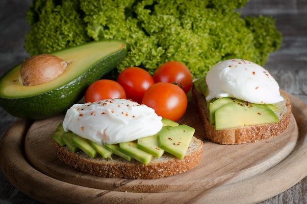 木製のアボカドトースト、チェリートマト、半熟卵。ベジタリアンフード、健康的な食事の朝食。