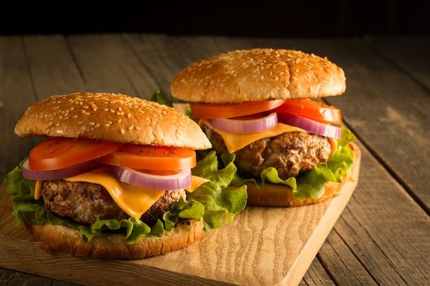 Домашний гамбургер с говядиной, луком, помидорами, листьями салата и сыром. свежий бургер заделывают на деревянный деревенский стол с картофелем фри, пиво и чипсы. чизбургер.