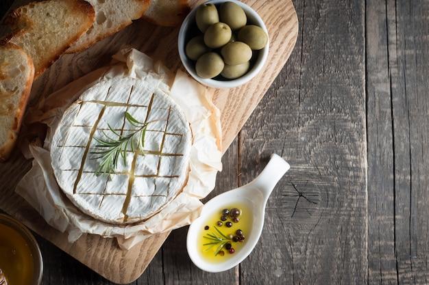 木製のカマンベールチーズとブリーチーズ、トマト、レタス、ニンニク。イタリア料理。乳製品。