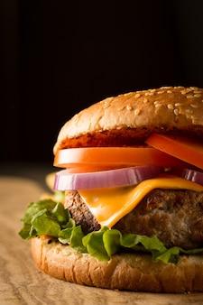 牛肉、玉ねぎ、トマト、レタス、チーズの自家製ハンバーグ。新鮮なハンバーガーは、ポテトフライ、ビール、チップスと木製の素朴なテーブルにクローズアップ。チーズバーガー。