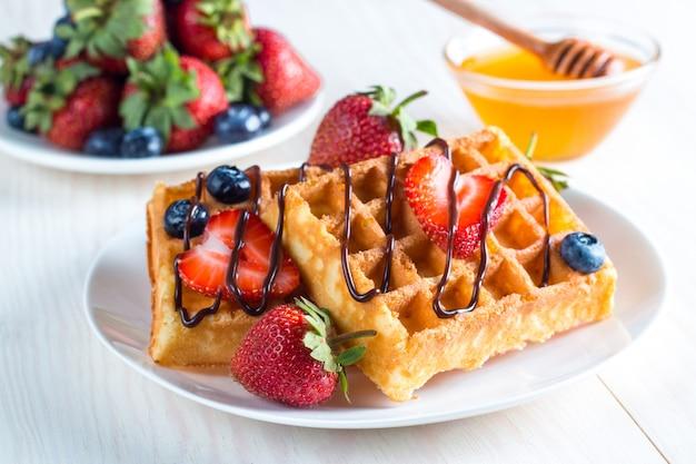 ベリーベルギーワッフル、蜂蜜、チョコレート、イチゴ、ブルーベリー、メープルシロップ、クリームの新鮮な自家製料理。ジュースと健康的なデザート朝食コンセプト