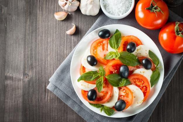 カプレーゼサラダとトマト、バジル、モッツァレラチーズ、オリーブ、オリーブオイルの写真。イタリアの伝統的なカプレーゼサラダの材料。地中海、オーガニック、自然食品のコンセプト。