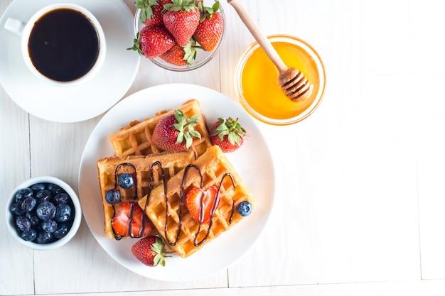 蜂蜜、チョコレート、イチゴ、ブルーベリー、メープルシロップ、クリーム入りのベリーベルギーワッフルの新鮮な自家製料理。ジュースと健康的なデザート朝食コンセプト