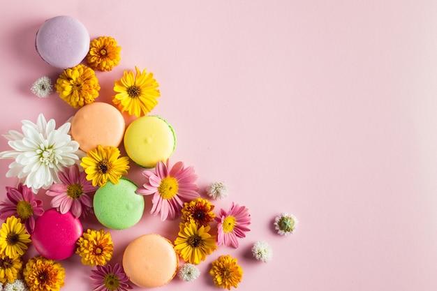花、明るい背景にお茶を一杯のギフトボックスにケーキマカロンの静物と食べ物の写真。マカロンのお菓子とデザートのコンセプト。