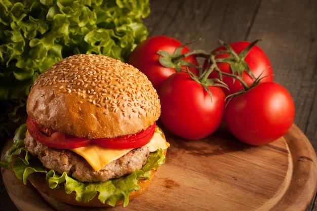 Домашний гамбургер с говядиной, луком, помидорами, листьями салата и сыром.