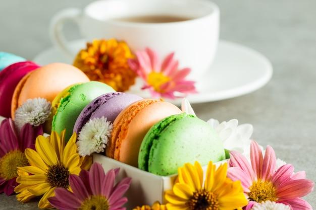 花、お茶とギフトボックスにケーキマカロンの静物と食べ物の写真