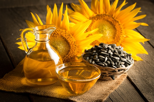 木製の背景に種子とひまわり油のクローズアップ写真。バイオおよびオーガニック製品のコンセプト。