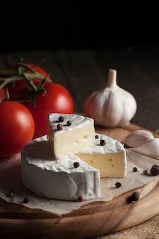 トマト、レタス、ニンニクと木製の背景にカマンベールとブリーチーズ。イタリア料理。乳製品。