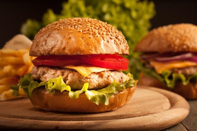 Домашний гамбургер с говядиной, луком, помидорами, листьями салата и сыром. чизбургер.