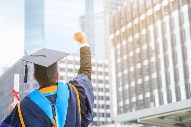 都市の卒業証書を手に保持している卒業ガウンで幸せなアジア男。