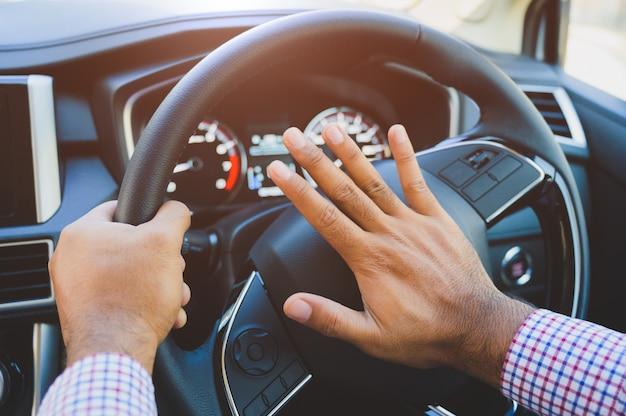 Рука человека толкает автомобильный гудок во время вождения автомобиля