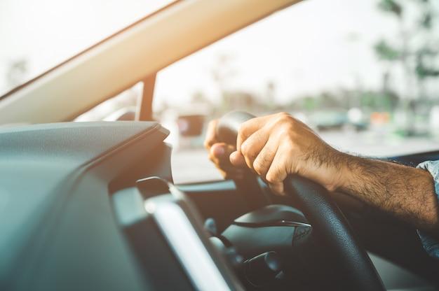手が車のステアリングホイールを握っています。