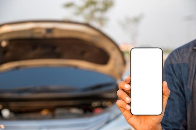 故障車の近くのスマートフォンの空白の画面