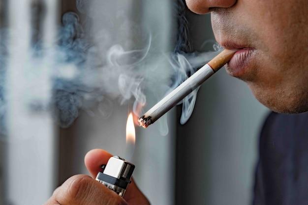 タバコを吸う若い男を閉じます。