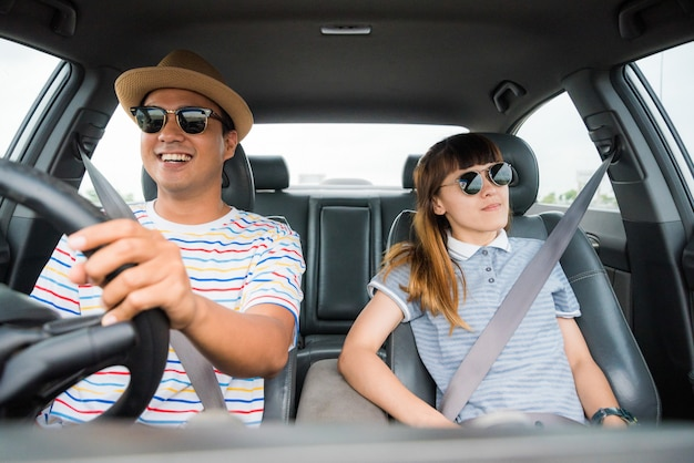 Вид спереди смешной момент пара азиатских мужчина и женщина, сидя в машине. наслаждаясь путешествия концепции.