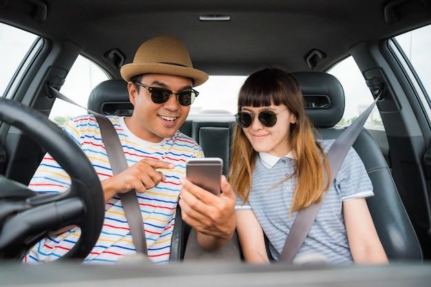 Соедините азиатского человека и женщину сидя в автомобиле и смотря телефон. концепция путешествия.