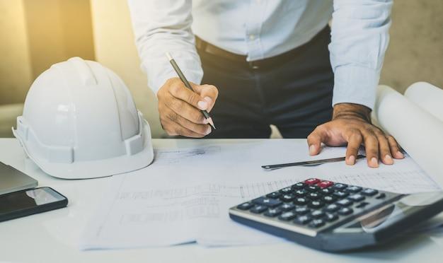 Инженер или архитекторы работают над планированием проекта на столе.