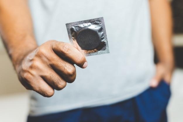 コンドームを持っている男性の手。安全なセックスの概念。
