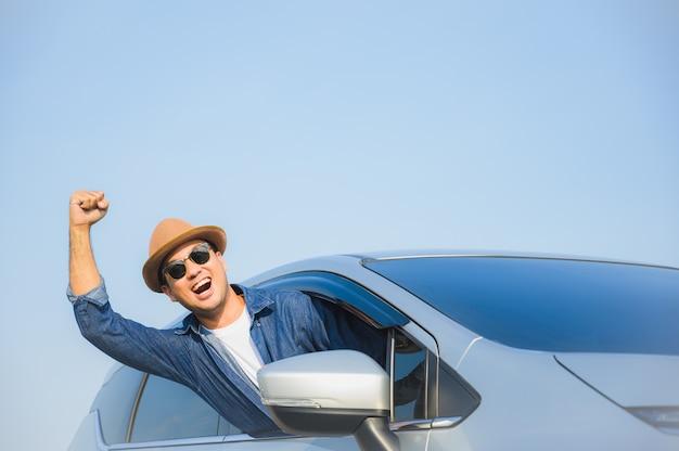 Молодой красивый азиатский человек управляя автомобилем, который нужно путешествовать на его отпуске с красивым голубым небом.