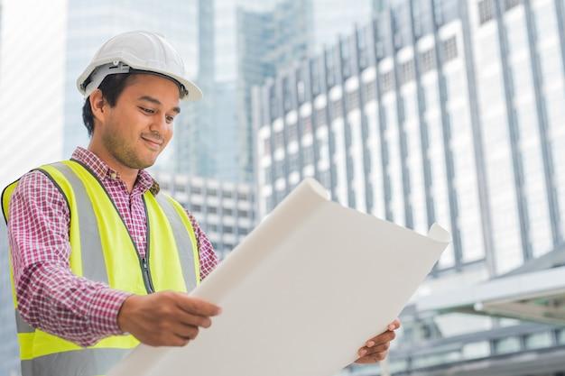Молодой азиатский инженер смотря и держа план плана здания