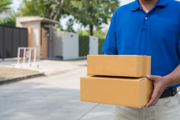 Конец вверх работник доставляющий покупки на дом в голубых формах держа пакет картонную коробку.