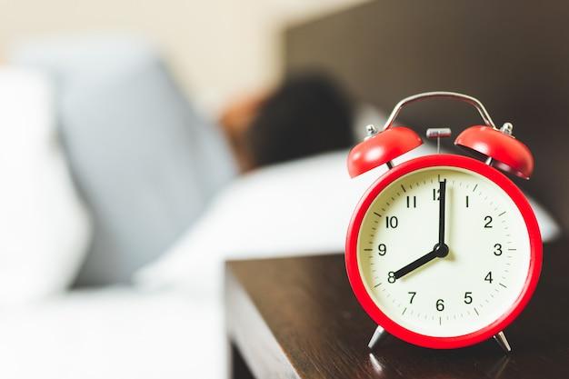目覚まし時計で寝ている男。