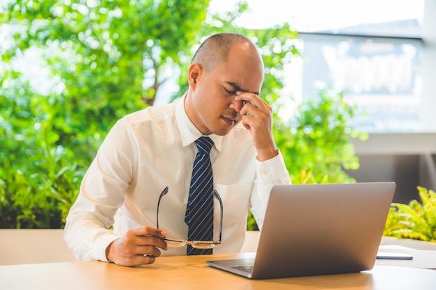 Усталый бизнесмен потирает глаза. офисный синдром концепции.