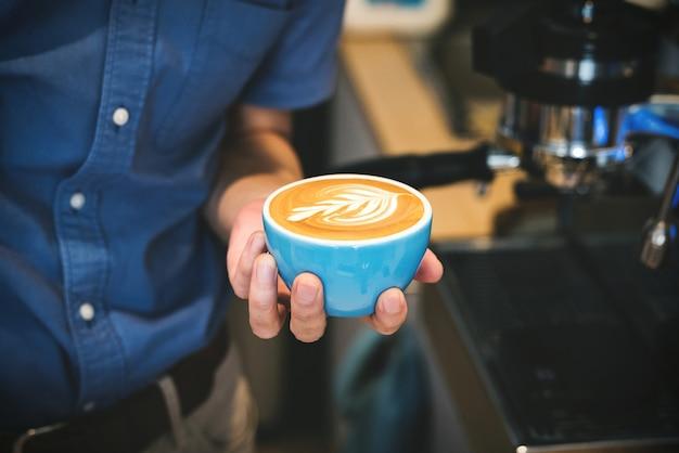 一杯のコーヒーを保持しているバリスタ