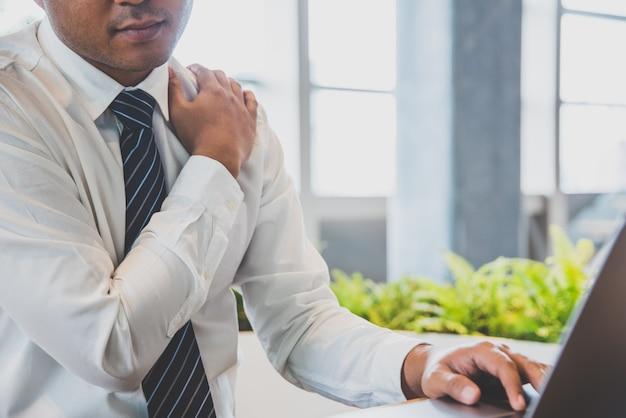 Предприниматель имеет боль в шее, плечо во время работы с ноутбуком. офисный синдром концепции.