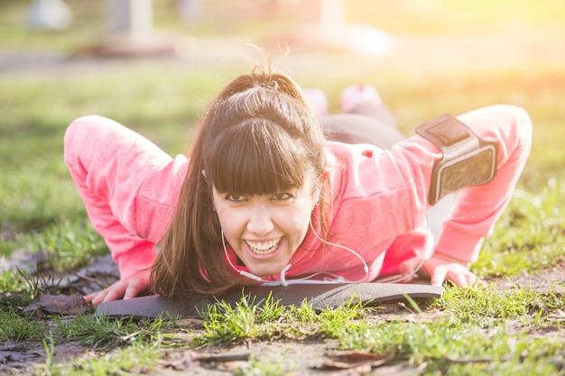 公園で腕立て伏せ運動をしている若い女性。