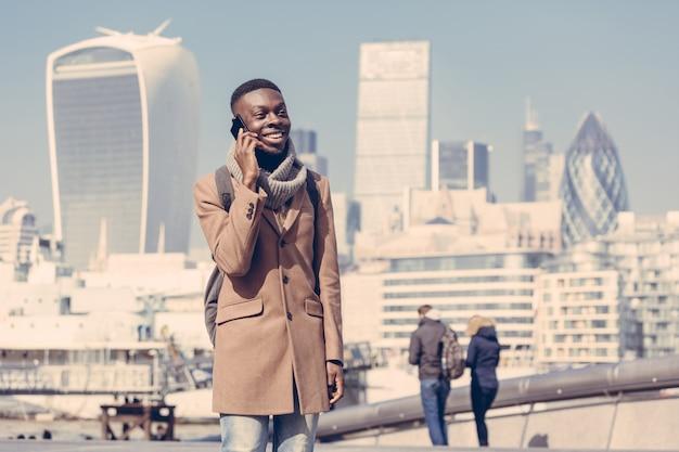 ロンドンの街と携帯電話で話している若い男