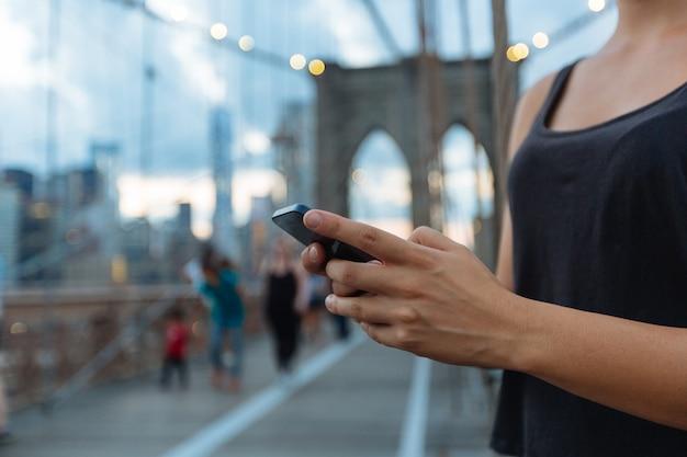 ブルックリン橋の上のスマートフォンを使用して若い女性