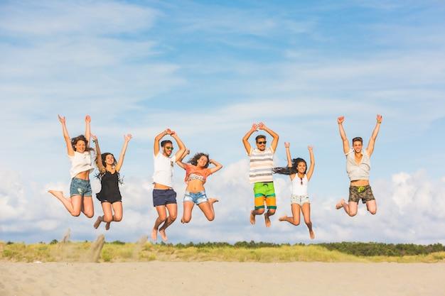 ビーチでジャンプ友達の多民族のグループ