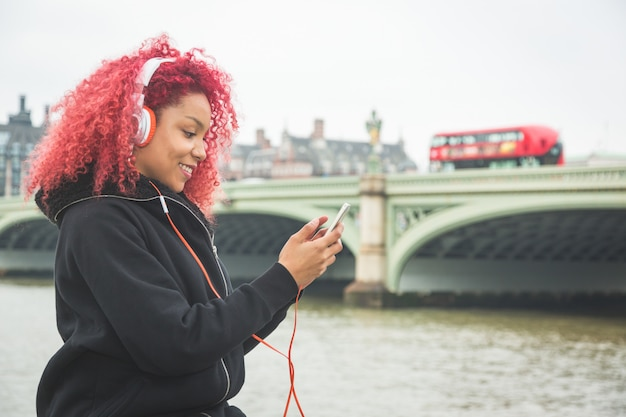 美しい女性がロンドンで音楽を聴く