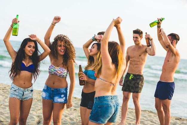 Многорасовая группа друзей, вечеринка на пляже